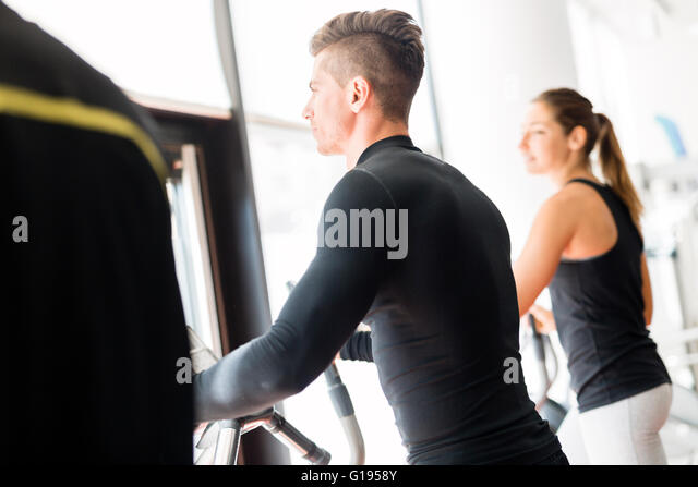 Young healthy group of people working out on a elliptic trainer in a fitness center - Stock Image