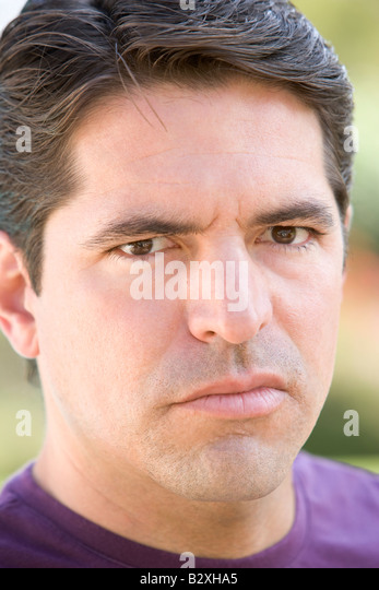 Head shot of man scowling - Stock Image