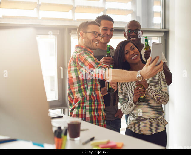 Diverse group of four happy young workers celebrating with beer and taking pictures with camera phone near desk - Stock Image