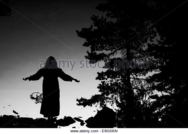 Reflection of silhouette woman with arms outstretched in lake - Stock Image