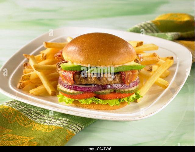 An avocado bacon burger on a bun with lettuce, tomato, pickle and onion served with french fries - Stock Image