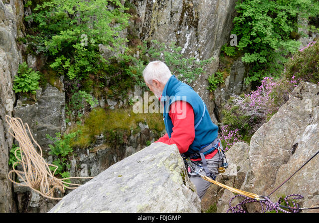 Experienced belayed rock climber throwing a climbing rope down from top of a crag climb. Snowdonia, North Wales, - Stock Image