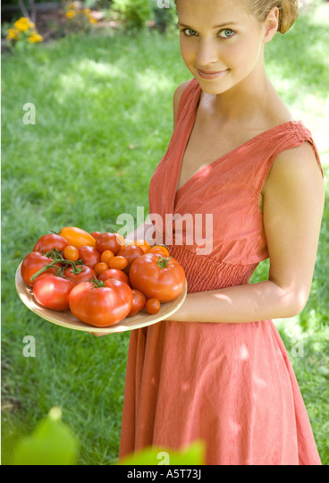 Woman holding bowl full of tomatoes - Stock Image