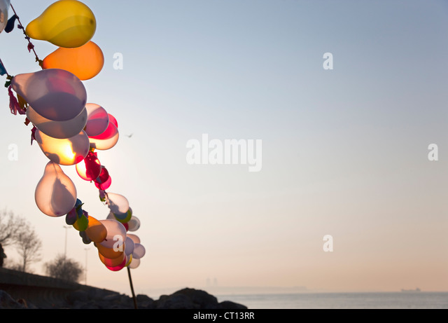 String of balloons floating in wind - Stock Image