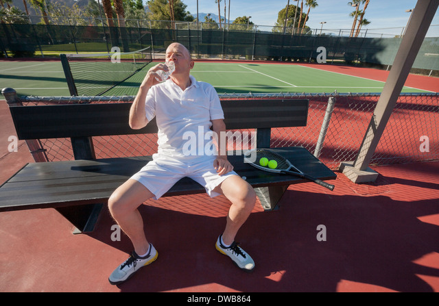 Senior male tennis player drinking water while relaxing on court - Stock Image