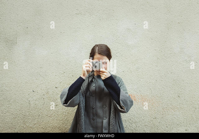 France, Languedoc-Roussillon, Sauve, Young tourist with camera against wall - Stock Image