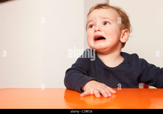 Little boy sitting on table crying - Stock Image