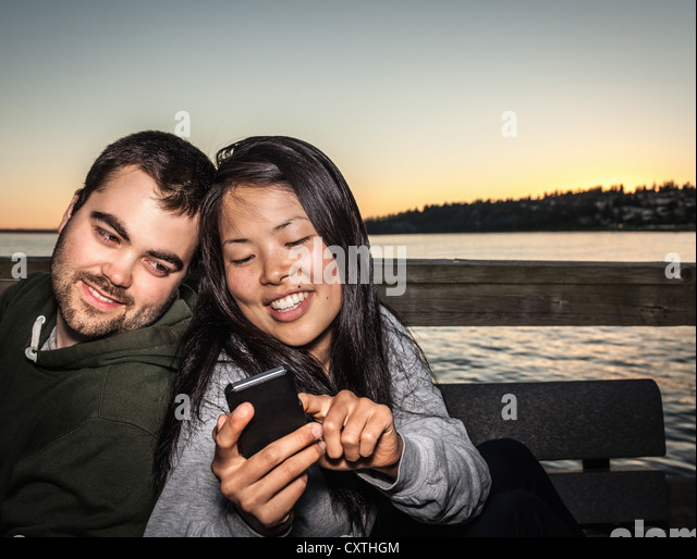 Couple using cell phone outdoors - Stock Image