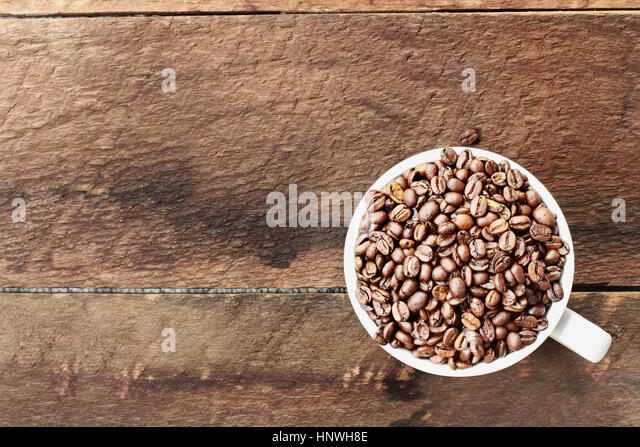 Overhead shot of a white cup filled with whole fresh coffee beans over a wood table top. Flat lay top view style. - Stock Image