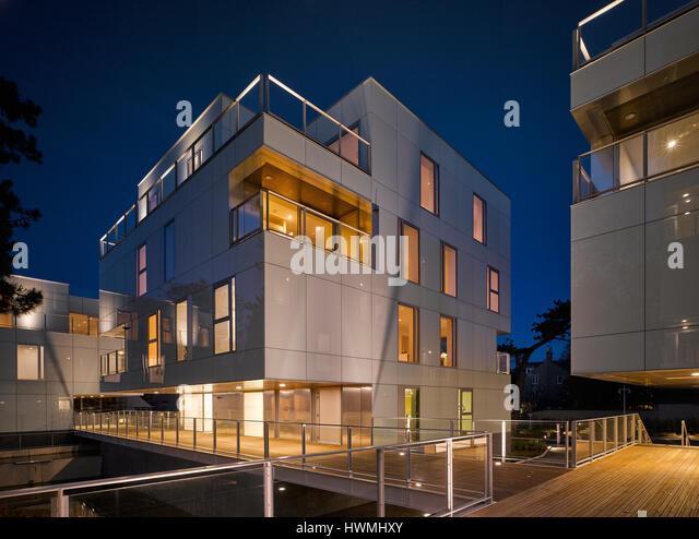 Night view of exterior showing lit interiors and walkway. Dunluce Apartments, Ballsbridge, Ireland. Architect: Derek - Stock-Bilder