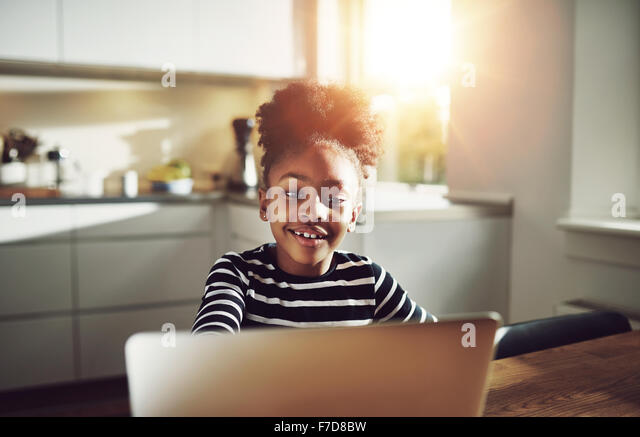 Cute young black girl playing on a laptop computer smiling happily as she surfs the internet while relaxing at a - Stock Image