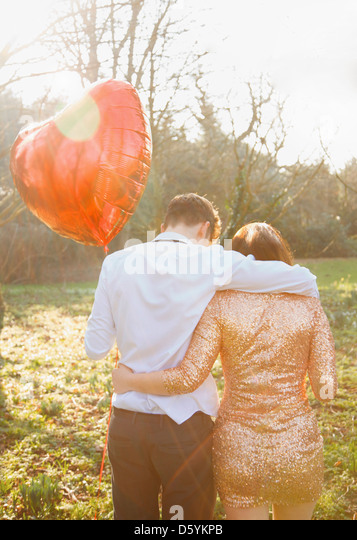 Couple in Park Holding Heart Shaped Balloon, Back View - Stock Image