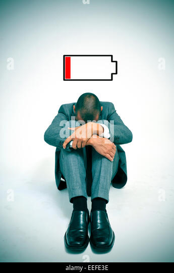 a young businessman curled up in the floor with his head between his knees and an illustration of a low battery - Stock Image
