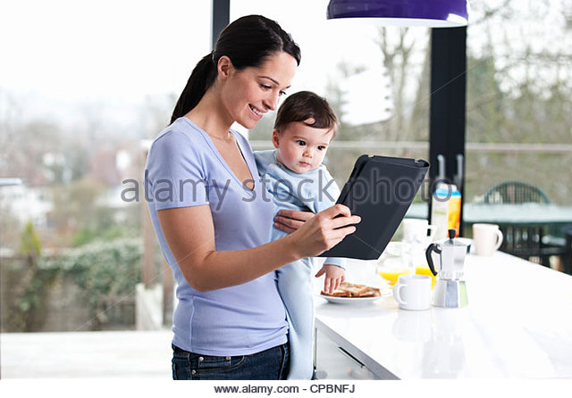A mother holding her baby son and looking at a digital tablet - Stock-Bilder