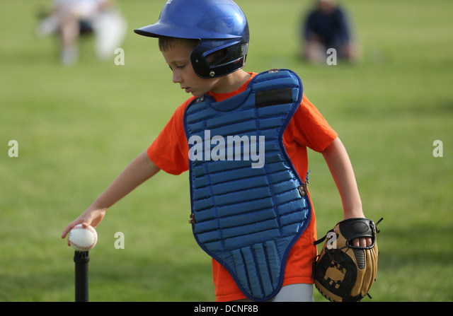Young boy puts baseball on tee - Stock Image