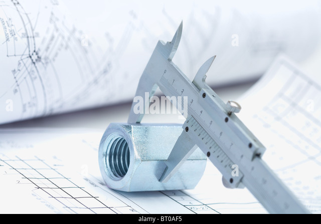 Image of architectural ruler over nut with house project near by - Stock-Bilder