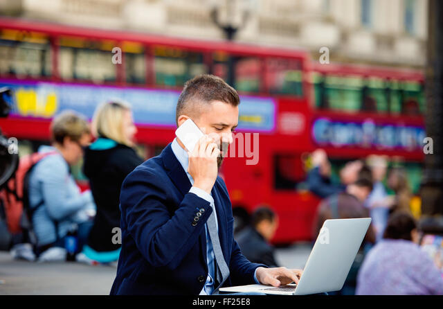 Manager with laptop and phone against  Londons red double-decker - Stock Image