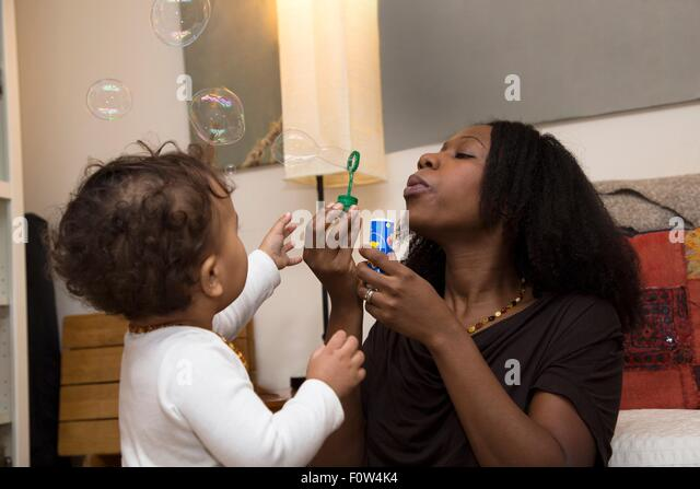 Mid adult woman and toddler daughter blowing bubbles - Stock Image