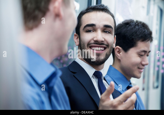 Three businessmen standing in a row and talking on the subway - Stock Image