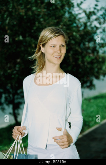 Woman carrying shopping bag, looking away and smiling - Stock Image