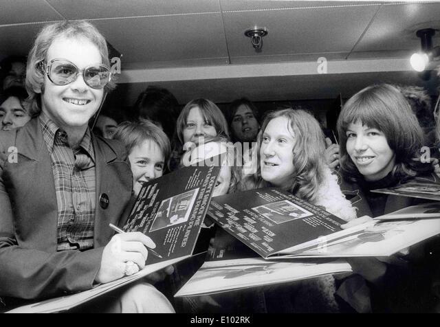 A young ELTON JOHN autographs albums for fans. - Stock Image