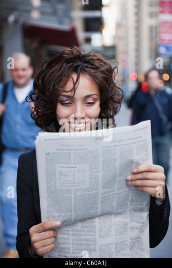 USA, New York, New York City, smiling businesswoman reading newspaper on street - Stock Image
