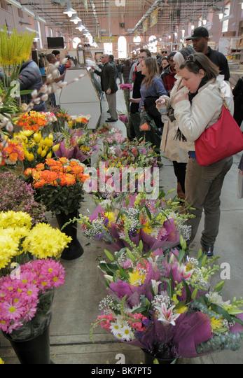 Washington DC Eastern Market 7th Street NE farmers market vendor fresh flowers bouquet shopping woman Black man - Stock Image