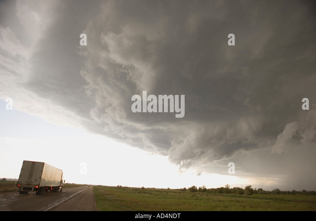 Storm clouds over a rural landscape and a semi-truck on a highway - Stock-Bilder