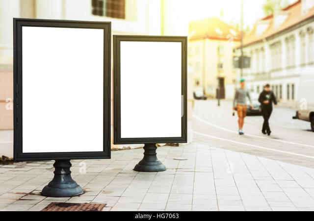 Two blank advertising billboards on the city street with pedestrians and sun glow - Stock Image