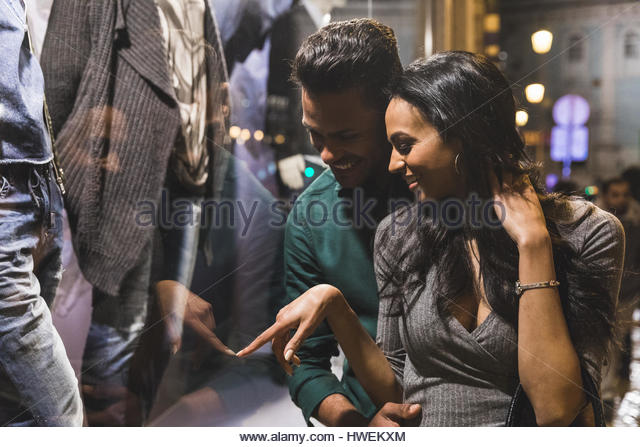 Couple in city at night, looking in shop window, Lisbon, Portugal - Stock-Bilder