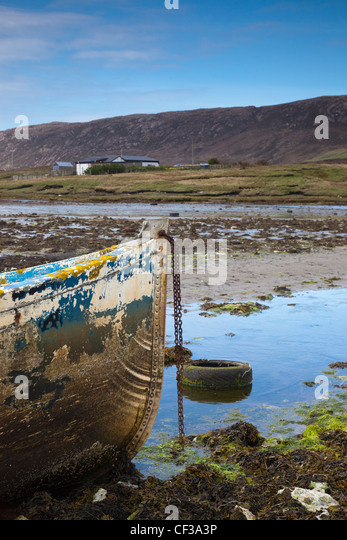 An Old Abandoned Rowboat In Shallow Water; Shetland Scotland - Stock Image