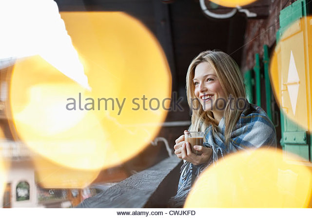 Smiling woman wrapped in a blanket and drinking coffee on cabin porch - Stock Image