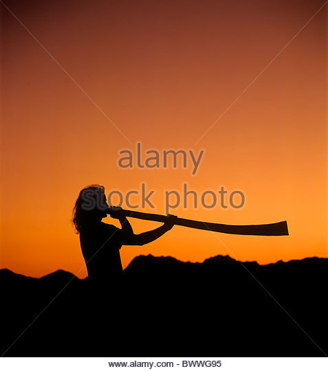 Man playing a didgeridoo at sunset with Tucson Mountains in background silhouette Orange and Black - Stock Image