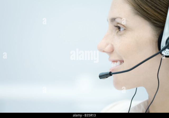 Young woman wearing headset, looking away and smiling, side view - Stock-Bilder