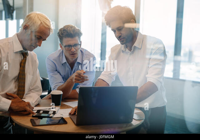 Business people talking while standing by table in office. Businessman giving demonstrating on laptop to colleagues - Stock Image