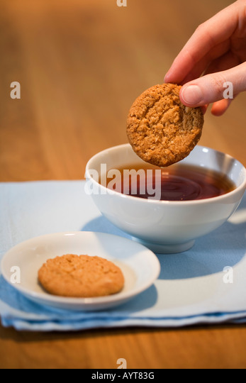 Hand putting some cakes into a tea - Stock Image