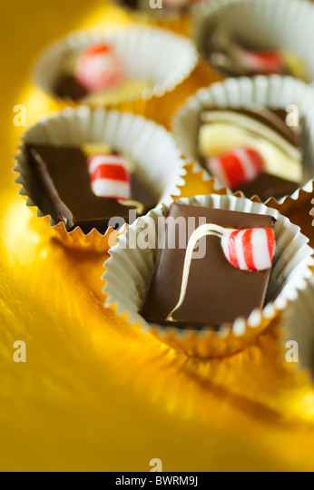 Double Chocolate Peppermint Bark broken in pieces and placed inside mini foil cups on a golden platter. - Stock Image