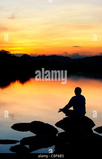 Sunrise silhouette of a man meditating on rocks at an Indian lake. Andhra Pradesh, India - Stock-Bilder