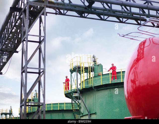 Workers on walkway of oil tank - Stock-Bilder