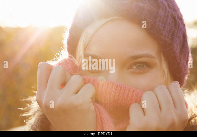 Portrait of young woman wearing knit hat, mouth covered - Stock Image