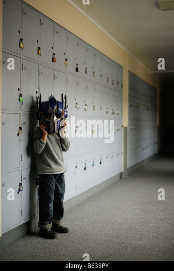 Boy in school corridor wearing Transformer robot mask - Stock Image