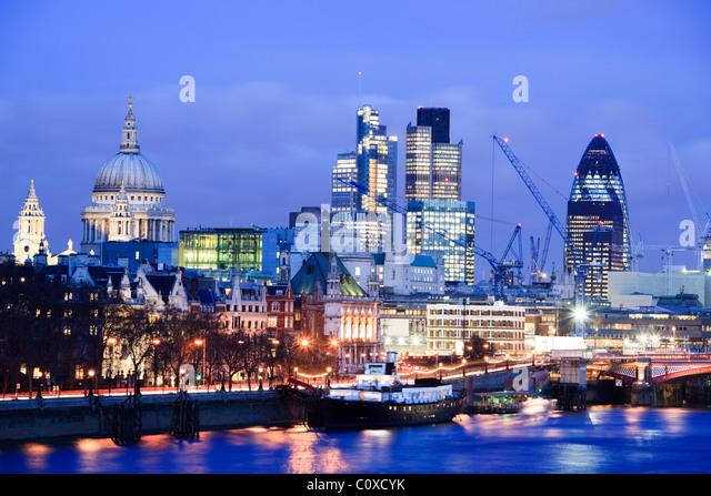 City Skyline viewed over river Thames at dusk; Dusk; London; UK - Stock Image