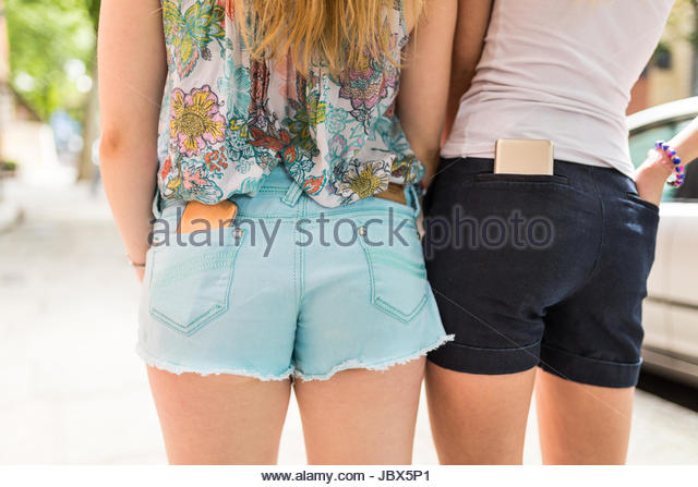Two female friends, outdoors, smartphones in back pockets, mid section, rear view - Stock-Bilder