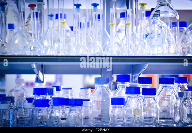 Glass bottles and jars beakers and test tubes with bright blue tops on shelf in science laboratory - Stock Image