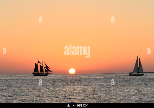 Sailboats in front of a beautiful Key West sunset. Taken from Malory Square - Stock Image