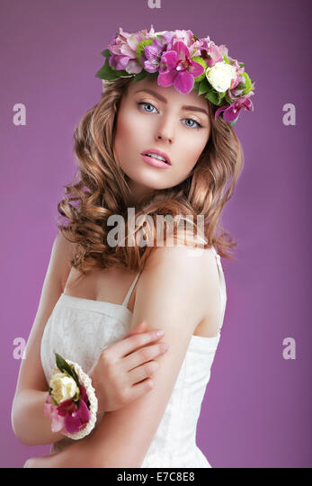 Exquisite Woman with Wreath of Flowers. Elegant Lady with Frizzy Hair - Stock Image