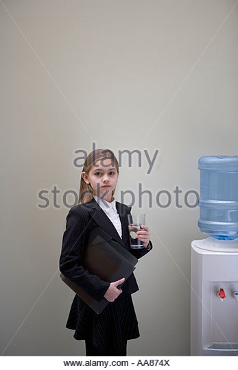 Young girl in business attire by the water cooler - Stock Image
