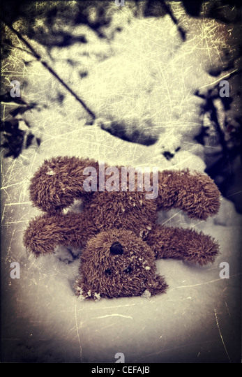 a forgotten teddy bear in the snow - Stock Image