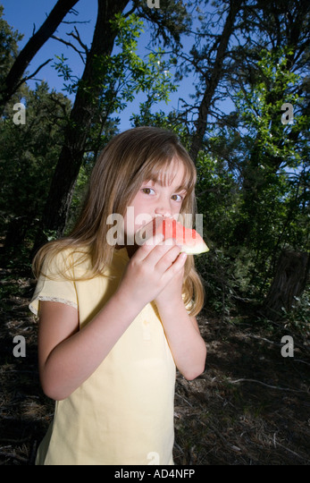A young girl eating a piece of watermelon in a forest - Stock-Bilder