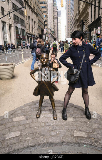 Tourists Posing with Fearless Girl Statue Staring Down the Charging Wall Street Bull, NYC, USA - Stock Image